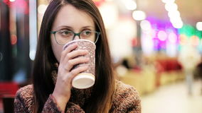 Beautiful Girl in Glasses Drinking Coffee in Cafe stock video