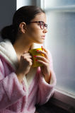Beautiful girl with glasses drinking morning coffee in front of window Stock Images