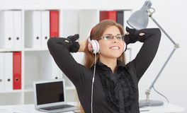 Beautiful girl in glasses with her hands behind her head listening to music on headphones. royalty free stock image