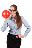 Girl with glasses inflating a red ball Stock Image