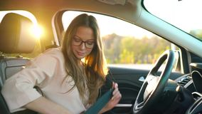 Beautiful girl with glasses inserted wireless headphones into her ears and fastened her seat belt about to drive away in. Beautiful woman with glasses inserted stock video