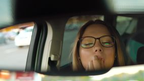 Beautiful girl in in glasses paints lips in the car and check her appearance in the mirror. Beautiful woman in in glasses paints lips in the car and check her stock video footage