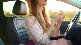 Beautiful girl in in glasses paints lips in the car and check her appearance in the mirror. Beautiful woman in in glasses paints lips in the car and check her stock footage