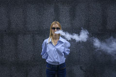 Beautiful girl in glasses with pleasure smokes a vape, day, outdoor. Teenage girl in a striped stylish shirt and jeans poses on the camera. Day, outdoor Royalty Free Stock Photography