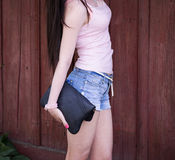 Beautiful girl with glasses shorts and pink blouse stands in front of a wooden fence, royalty free stock image