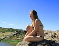 Beautiful girl in glasses sits highly on a stone Royalty Free Stock Images