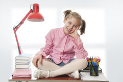 Girl with glasses sitting on a desk Stock Images