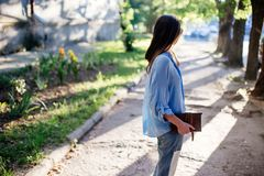 Girl is holding a clutch bag. A beautiful girl with glasses on the street holds a clutch bag in her hands. Summer evening, sunset royalty free stock photo