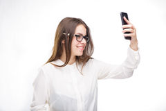 Beautiful girl in glasses and a white shirt takes a picture of herself on the camera phone, selfie on white isolated background. Beautiful girl in glasses and a Royalty Free Stock Photo
