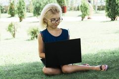 A beautiful girl in glasses works on a compute, outside. The student makes lessons on a laptop stock photography