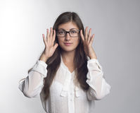 Beautiful girl with glasses. Beautiful young woman showing hands on the glasses that her dressed Royalty Free Stock Photography