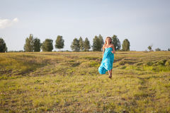 Beautiful girl goes on field, summer Royalty Free Stock Photo