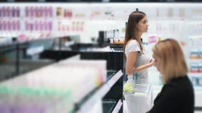 Beautiful girl goes among shelves in cosmetics shop, slow motion, steadicam shot. Beautiful girl goes among shelves in cosmetics shop, slow motion. Steadicam stock video