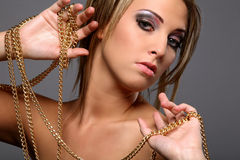Beautiful girl with gold chain. Isolated on gray background Royalty Free Stock Images