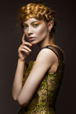 Beautiful girl in a gold dress with creative makeup and braids on her head. The beauty of the face. Royalty Free Stock Image