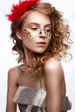 Beautiful girl in a gold dress with a gentle make-up. Model with red feathers on her head and curls. Holiday photo. Royalty Free Stock Photography