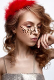 Beautiful girl in a gold dress with a gentle make-up. Model with red feathers on her head and curls. Holiday photo. Stock Images