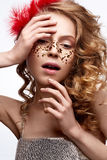 Beautiful girl in a gold dress with a gentle make-up. Model with red feathers on her head and curls. Holiday photo. Stock Photos