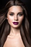 Beautiful girl with golden makeup and burgundy lips with the wind in hair. Beauty face. Picture taken in the studio on a black background Stock Images