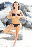 Beautiful girl in good shape doing yoga by the rocks Stock Image