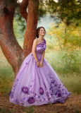 Beautiful girl in a gorgeous purple dress standing under a tree royalty free stock image