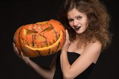 Beautiful girl with a make-up as a witch smiles and holds an orange pumpkin on a black background for the holiday of Halloween royalty free stock photo