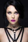Beautiful Girl in the Gothic style with leather accessories and bright makeup. Beauty face. Royalty Free Stock Photo