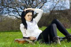 The beautiful girl on a grass with a guitar Stock Images