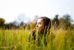Beautiful  girl through the grass in a meadow. Dreaming beautiful girl lying in a meadow. view through the grass Stock Image