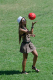 Beautiful girl on grass playing red ball Royalty Free Stock Photos
