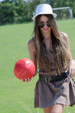 Beautiful girl on grass playing red ball Stock Photos