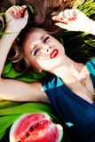 Beautiful girl in the grass with watermelons. Beautiful girl with red lips in the grass with watermelons Stock Image