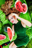 Beautiful girl in the grass with watermelons. Beautiful girl with red lips in the grass with watermelons Royalty Free Stock Photography