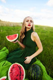 Beautiful girl in the grass with watermelons Royalty Free Stock Photos