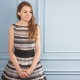 Beautiful girl in a gray dress near blue wall. Beautiful girl in a gray dress near a blue wall. Square frame Royalty Free Stock Photography