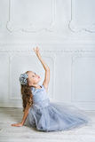 Beautiful girl in gray dress and pointe shoes is posing on the f Stock Photo
