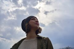 Beautiful girl in gray hat on sky background. Portrait of young woman freedom conception