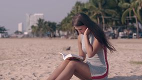 Girl in gray summer dress with red and white stripes on sand. Beautiful girl in gray summer dress with red and white stripes sits on sandy beach and reads book stock video footage