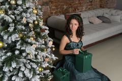 Beautiful girl in a green dress, with black curls. At a Christmas tree with a giftn stock photo