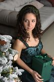 Beautiful girl in a green dress, with black curls. At a Christmas tree with a giftn stock images