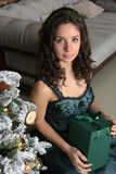 Beautiful girl in a green dress, with black curls. At a Christmas tree with a giftn stock image