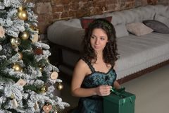 Beautiful girl in a green dress, with black curls. At a Christmas tree with a giftn royalty free stock photos