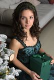 Beautiful girl in a green dress, with black curls. At a Christmas tree with a giftn royalty free stock photography
