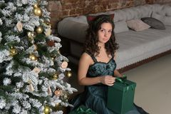 Beautiful girl in a green dress, with black curls. At a Christmas tree with a giftn royalty free stock photo