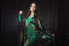 Beautiful girl in green dress dancing Oriental dance Stock Image