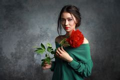 Beautiful girl in the green dress with flowers peonies in hands on a light gray background. Joyful Asian female model posing in royalty free stock photos