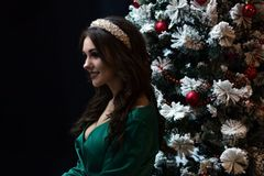 Beautiful girl in a green dress near the New Year tree on a black background. Beautiful girl in a green dress near the New Year tree on a black background Royalty Free Stock Photos