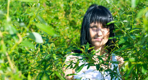 Beautiful girl in green foliage Royalty Free Stock Image