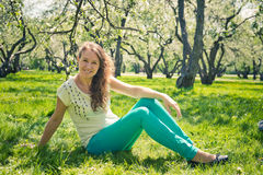 Beautiful  girl in green jeans sits Stock Image