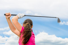 Beautiful girl on a green lawn with a golf club Royalty Free Stock Photos